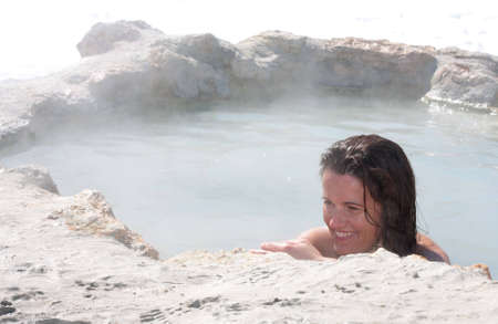 A woman has a relaxing soak in a natural hot spring in central california.