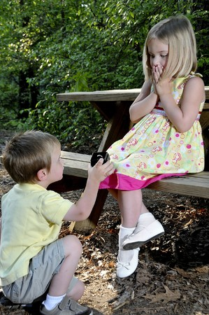 A little boy proposing marriage to a little girl