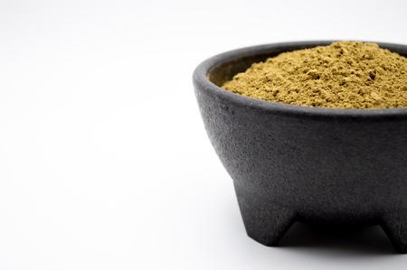 Foto de Bulk Kratom powder in a black bowl isolated on a white background. - Imagen libre de derechos