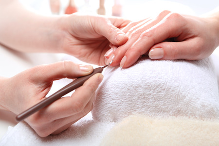Manicure, cutting skins woman to a beautician