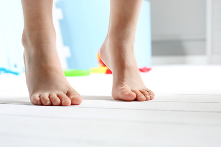Photo pour Childrens bare feet. Childs bare feet on the wooden floor - image libre de droit