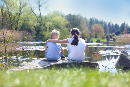 Two children older sister and younger brother sitting on the shore of the lake
