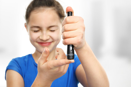 Photo for Girl with diabetes is a measure of blood sugar levels using a glucometer - Royalty Free Image
