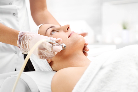 Photo pour Diamond microdermabrasion. Relaxed woman during a microdermabrasion treatment in beauty salon - image libre de droit