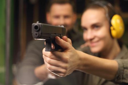 Foto de Woman shoots a gun at a shooting range. - Imagen libre de derechos
