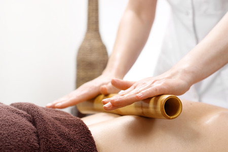Foto per Bamboo massage. The masseur massages the body using bamboo sticks. - Immagine Royalty Free