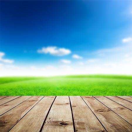Photo pour Green field under blue sky. Wood planks floor. Beauty nature background - image libre de droit
