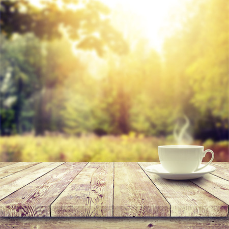 Foto de Cup with hot drink on wood table over forest  background - Imagen libre de derechos