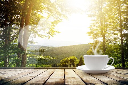 Foto de Cup with tea on table over mountains landscape with sunlight. Beauty nature background - Imagen libre de derechos