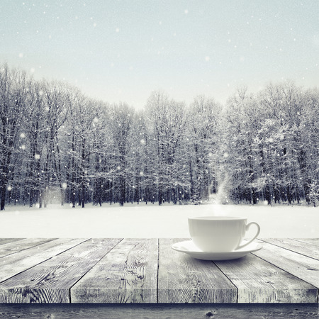Foto de Hot drink in the cup on wooden table over winter snow covered forest. Beauty nature background - Imagen libre de derechos