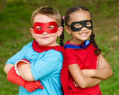 Pretty mixed race girl and Caucasian boy pretending to be superhero