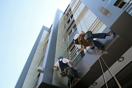 Photo pour Workers washing the windows facade of a modern office building  - image libre de droit