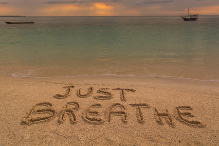 Photo for In the picture a beach at sunset with the words on the sand Just breathe. - Royalty Free Image