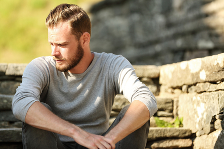 Photo pour Man in his 20s wearing a grey shirt and jeans, sitting down outside on a set of steps on a sunny summer day. - image libre de droit