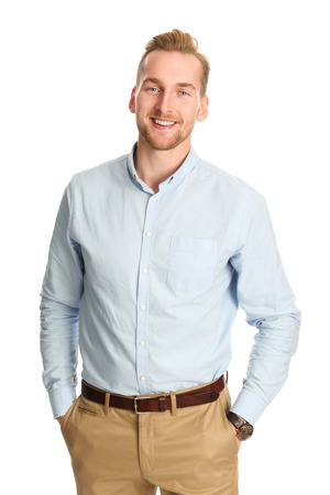 Photo for An attractive young man wearing a blue shirt with khaki pants, standing smiling towards camera against a white background. - Royalty Free Image