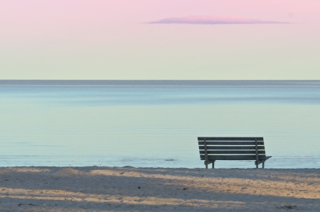 Foto de Bench on a sandy beach in the evening - Imagen libre de derechos