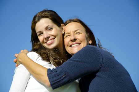 Beautiful mother and daughter hugging each other on a sunny  day outside, with clear blue sky as background and copy space