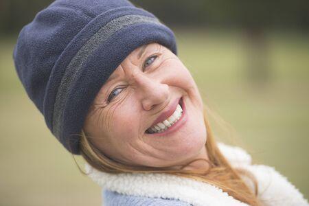 Portrait joyful confident attractive mature woman outdoor, wearing warm bonnet and wool jacket, blurred green background.