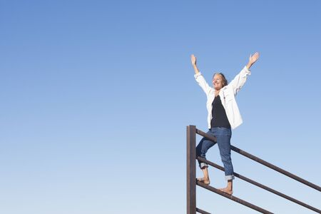 Portrait attractive senior woman standing in winning pose on top of metal fence, happy smiling, arms up and joyful, with blue sky as background and copy space.