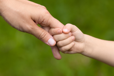 Photo for Mother holding a hand of her daughter on blurred background, closeup - Royalty Free Image