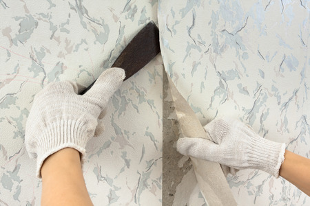 Foto de hands in glove removing old wallpaper with spatula during repair - Imagen libre de derechos