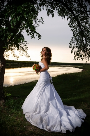 Photo pour The bride at the riverside under the arch of branches - image libre de droit