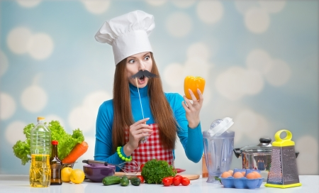 Humorous portrait of a woman in chef hat with paper mustache looking at the pepper in her hand