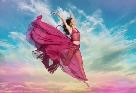 Photo for Woman in airy crimson dress jumping in the air at sunset - Royalty Free Image