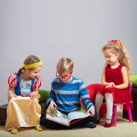 Preteen boy reading a fairy tale to two little girls