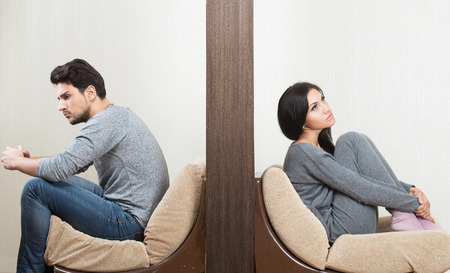 Photo pour Conflict between man and woman sitting on either side of a wall - image libre de droit