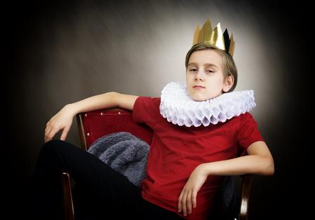 Foto de Crowned boy sitting in an armchair - Imagen libre de derechos