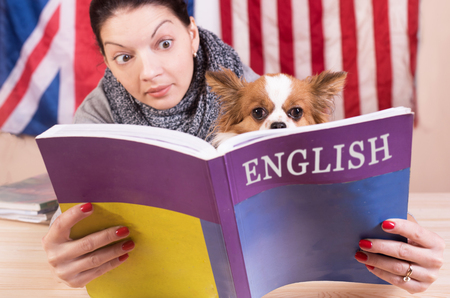 Foto de Simple learning language concept. English even for dog. Young woman and her dog learning english language. - Imagen libre de derechos