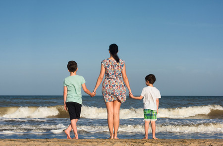 Photo for Mother and her sons look at the ocean. - Royalty Free Image