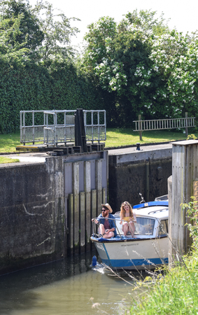 Foto de Culham, United Kingdom - May 07 2018:   A young couple sit on the prow of a cruiser boat as it comes out of Culham Lock - Imagen libre de derechos