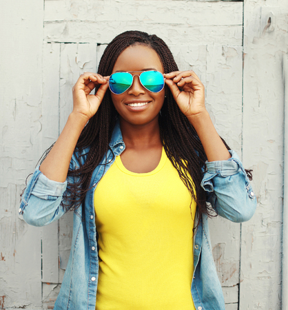 Photo pour Portrait happy smiling african woman in colorful clothes and sunglasses - image libre de droit