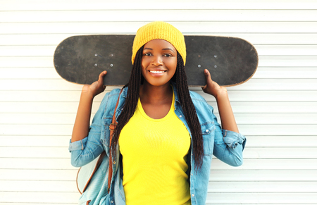 Photo pour Fashion pretty young smiling african woman with skateboard in colorful clothes over white background - image libre de droit