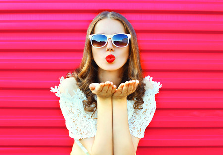 Photo for Woman in sunglasses sends an air kiss over colorful pink background - Royalty Free Image