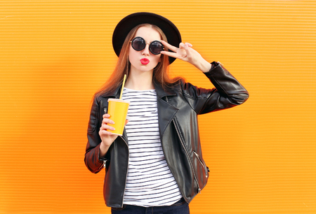 Fashion pretty woman in black rock style having fun over orange background