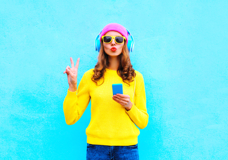 Photo for Fashion pretty sweet carefree woman listening music in headphones with smartphone wearing a colorful pink hat yellow sweater sunglasses over blue background - Royalty Free Image