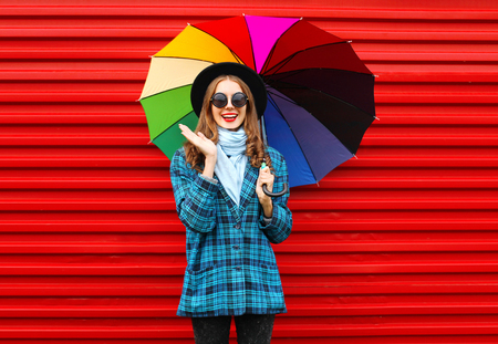 Photo for Fashion cheerful smiling woman holds colorful umbrella wearing black hat checkered coat jacket over red background - Royalty Free Image