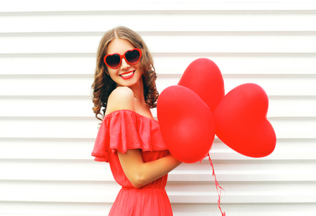 Photo for Happy smiling young woman wearing red dress and sunglasses with air balloons heart shape over white background - Royalty Free Image