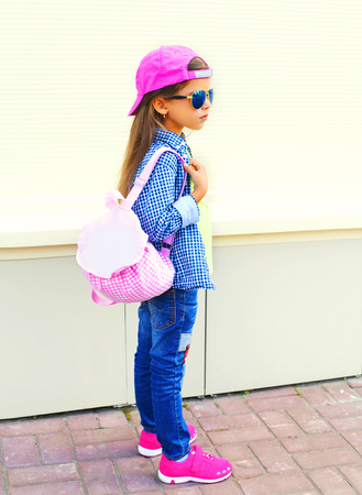 Photo pour Fashion kid little girl wearing a baseball cap and backpack in the city on a white background - image libre de droit