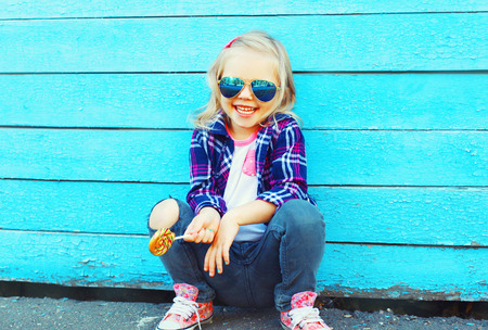 Photo for Fashion portrait happy smiling little girl child with a lollipop stick having fun - Royalty Free Image