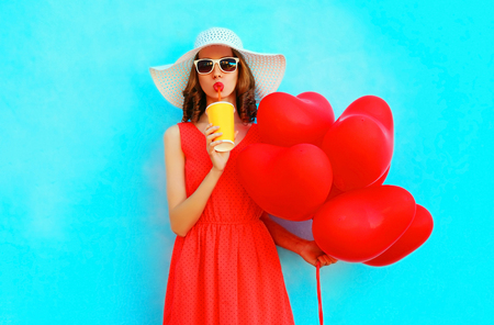 Photo pour Portrait woman in summer hat drinks juice from cup with red an air balloons on blue background - image libre de droit