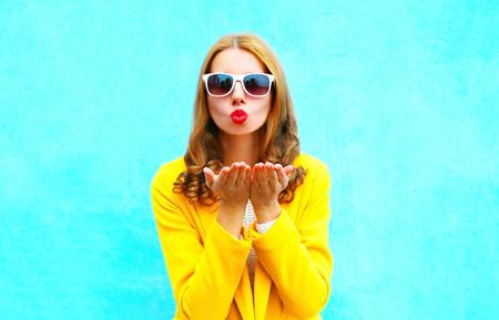 Photo pour Beautiful woman sends an air kiss in yellow coat on colorful blue background close-up - image libre de droit