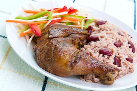 Caribbean style jerk chicken served with rice mixed with red kidney beans. Dish accompanied with vegetable salad.