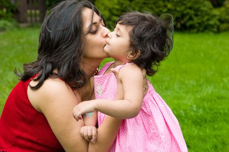 A mother plays kisses her daughter in the backyard