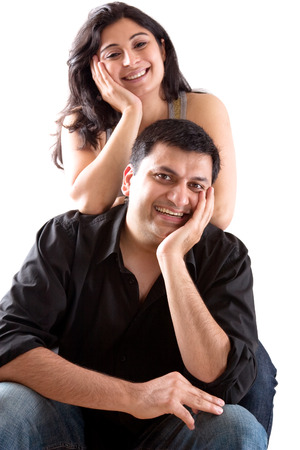 An East Indian man embraces his pregnant wife
