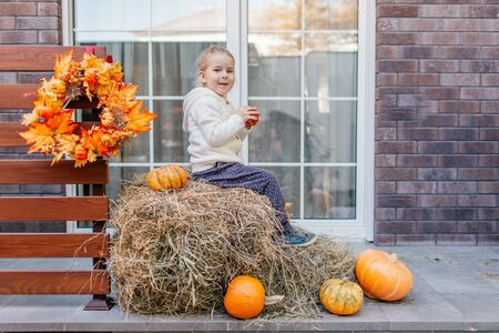 Photo for Adorable blonde baby toddler in white knittes jacket sitting on the haystack with pumpkins at porch, playing with apple and laughing. Halloween Thanksgiving card. - Royalty Free Image