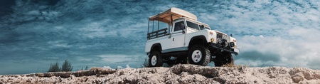 Foto de Panoramic photo of safari car on offroad , adventure trail. On high, Bottom view, sky and clouds on background, With empty space for logo or text - Imagen libre de derechos